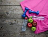 Las pesas de gimnasia coloreadas de las manzanas se divierten las botellas de agua y la toalla rosada imagen de archivo libre de regalías