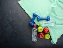 Las pesas de gimnasia coloreadas de las manzanas se divierten las botellas de agua y la toalla de la turquesa fotografía de archivo libre de regalías