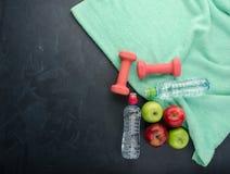 Las pesas de gimnasia coloreadas de las manzanas se divierten las botellas de agua y la toalla de la turquesa foto de archivo libre de regalías