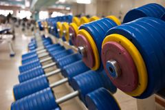 Las pesas de gimnasia con los discos amarillos y rojos del cargo en el gimnasio mienten en fila Fondo fotografía de archivo libre de regalías