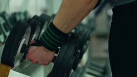Las pesas de gimnasia de la toma de las manos del hombre del gimnasio se colocan, se cierran encima de tiro metrajes