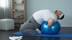 Las pesas de gimnasia de elevación que mienten en bola de la aptitud, músculos del varón gordo útil bombean almacen de metraje de vídeo
