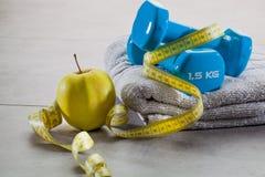 Las pesas de gimnasia, la manzana, la toalla y la cinta métrica para el cuerpo de dieta cuidan Imagen de archivo