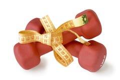 Las pesas de gimnasia rojas ataron a la cinta métrica Foto de archivo