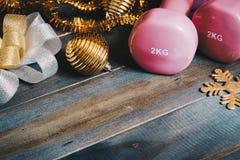 Las pesas de gimnasia rosadas del deporte con los artículos de la decoración de Chrismas y el regalo arquean fotos de archivo