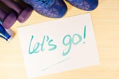 Las pesas de gimnasia se divierten las botellas de zapatos del agua y del deporte en un fondo de madera Fotos de archivo libres de regalías
