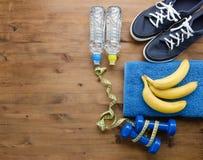 Las pesas de gimnasia de las zapatillas de deporte miden la botella de la toalla de la cinta de agua y de plátano foto de archivo libre de regalías