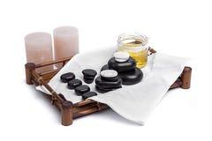 Las piedras aisladas del masaje fijaron con las velas, el aceite y las toallas Imágenes de archivo libres de regalías