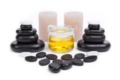 Las piedras aisladas del masaje fijaron con las velas y el aceite Imagen de archivo libre de regalías