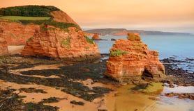 Las piedras areniscas rojas impresionantes del Ladram aúllan en la costa jurásica, un sitio del patrimonio mundial en la costa de fotos de archivo