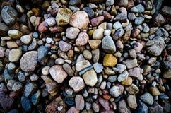 Las piedras coloridas lisas hermosas en el mar del verano varan Fotos de archivo libres de regalías