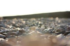 Las piedras en la costa, costa costa, los rayos del sol Imagen de archivo libre de regalías