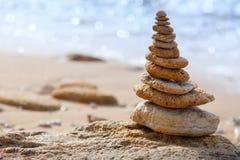 Las piedras equilibran y mar azul en fondo defocused Imagen de archivo