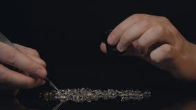 Las piedras preciosas del tasador vierten diamantes y cristales en la tabla y valoran su almacen de video