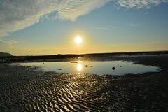 Las piedras se pegan en un charco mientras que una puesta del sol Imágenes de archivo libres de regalías