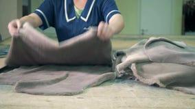 Las pieles forradas de piel están siendo enderezadas hacia fuera por las manos de un trabajador de sexo femenino metrajes