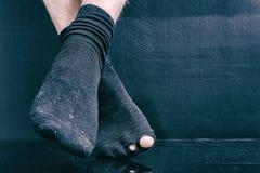 Las piernas arruinan en calcetines holey negros en un fondo negro Fotografía de archivo