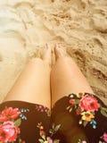 Las piernas bronceadas en el verano asolean pies en la arena en la playa Fotografía de archivo libre de regalías