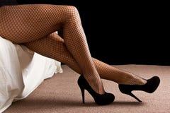 Las piernas con alto negro curan los zapatos Foto de archivo