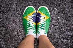Las piernas con los zapatos del deporte colorearon la bandera brasileña Fotos de archivo