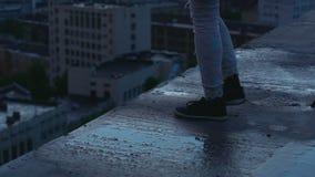 Las piernas de la hembra adolescente vienen muy cercano al borde constructivo listo para el salto del suicidio metrajes