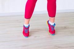 Las piernas de la muchacha de la aptitud en polainas rojas y zapatillas de deporte, colocándose de puntillas Foto de archivo libre de regalías