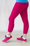 Las piernas de la muchacha de la aptitud en polainas y zapatillas de deporte rojas Fotografía de archivo libre de regalías
