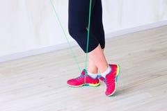 Las piernas de la muchacha de la aptitud en polainas y zapatillas de deporte rojas Imágenes de archivo libres de regalías
