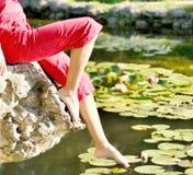 Las piernas de la muchacha en agua en parque del verano Fotos de archivo libres de regalías