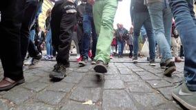 Las piernas de la muchedumbre de gente cruzan el camino en un paso de peatones almacen de metraje de vídeo