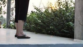 Las piernas de la mujer asiática en sandalias negras y una escoba arrebatadora en balcón metrajes