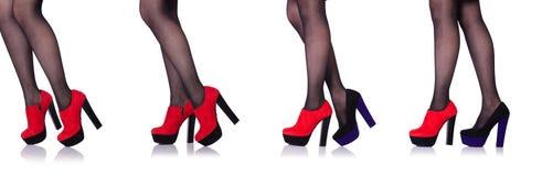 Las piernas de la mujer con los zapatos rojos aislados en el blanco foto de archivo