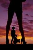 Las piernas de la mujer de la silueta con de los talones la silla de montar del vaquero lejos Fotos de archivo libres de regalías