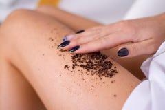 las piernas de la mujer del primer con masaje del café friegan Cosmetología, preparación, productos cosméticos del balneario, bel fotografía de archivo libre de regalías