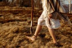 Las piernas de la mujer en boho americano indio nativo visten caminar en ventoso Imagen de archivo libre de regalías