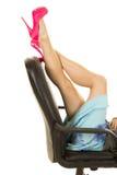 Las piernas de la mujer en talones rosados ponen en silla de la oficina detrás foto de archivo