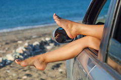 Las piernas de la mujer que cuelgan hacia fuera una ventanilla del coche Foto de archivo libre de regalías