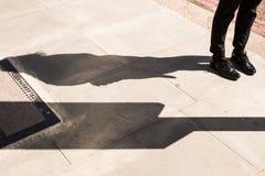 Las piernas de la mujer que llevan Londres diseñan abarcas de cuero negras Fotos de archivo libres de regalías