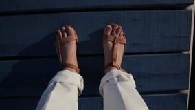 Las piernas de la mujer que se coloca en el embarcadero de madera azul marino y revuelve sus dedos del pie almacen de metraje de vídeo