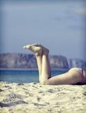 Las piernas de las mujeres en la playa Fotografía de archivo libre de regalías