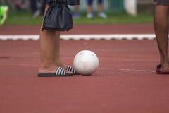 Las piernas de los hombres con el balón de fútbol blanco fotografía de archivo