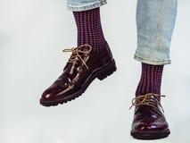 Las piernas de los hombres, zapatos elegantes y calcetines divertidos imagenes de archivo