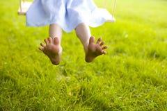 Las piernas de los niños graciosamente con los fingeres anchos de la extensión Fotos de archivo