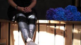 Las piernas de las mujeres en pantalones de cuero negros Muchacha atractiva que se sienta en contador de la barra y las piernas d almacen de metraje de vídeo
