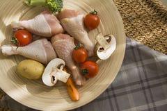 Las piernas de pollo en la placa simple en día se encienden Foto de archivo libre de regalías