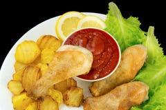 Las piernas de pollo sumergieron en salsa de tomate en una placa blanca con lechuga y asaron la opinión de las patatas desde arri Foto de archivo