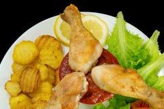 Las piernas de pollo sumergieron en salsa de tomate en una placa blanca con lechuga y asaron la opinión de las patatas desde arri Imágenes de archivo libres de regalías