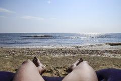 Las piernas de un hombre en un fondo de la playa Un hombre miente en un amatra fotos de archivo libres de regalías