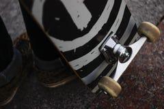 Las piernas de un individuo en zapatillas de deporte con un monopatín en la calle Primer de la rueda y de la suspensión del patín Fotografía de archivo