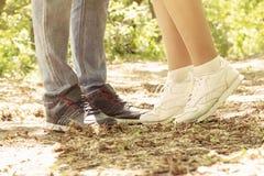 Las piernas de un individuo y de una muchacha que besan a la muchacha están en sus calcetines imagen de archivo